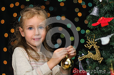 Little girl decorates tree