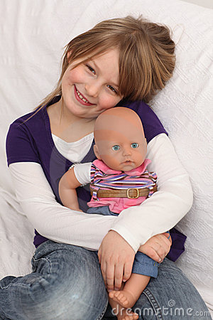 Little girl with doll on sofa