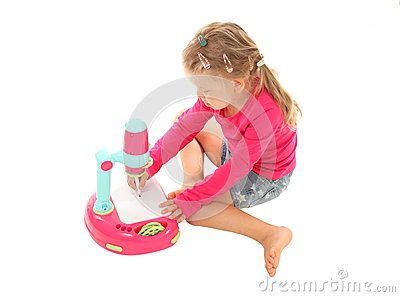 Little girl drawing picture with a toy projector