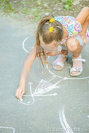 Little girl draws with chalk