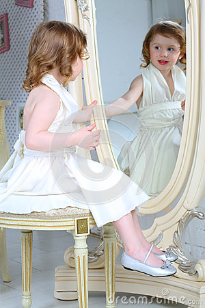 Free Little Girl Dressed Admires Her Reflection In Mirror Royalty Free Stock Photo - 34053355