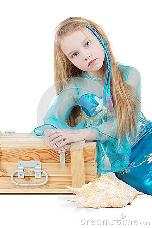 Little girl dressed as mermaid sits near to chest