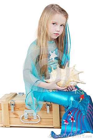 Little girl dressed as mermaid sits with seashell