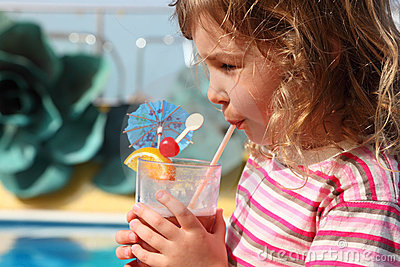 Little girl drinking cocktail with fruits