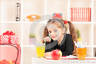 Little girl drinking a juice at home