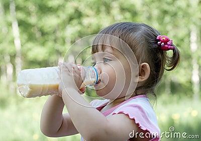 Little girl drinking milk outdoor in Summer
