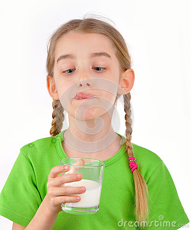 Little girl drinks milk from a glass