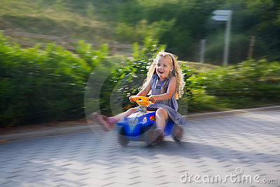 Little girl driving with a toy car