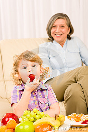 Little girl eat strawberry fruit with grandmother