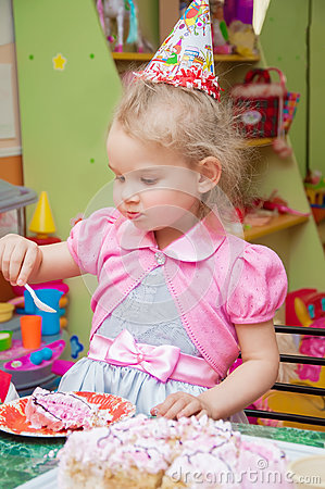 Little girl eating cake at birthday party