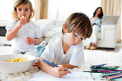 Little girl eating chips and her brother drawing