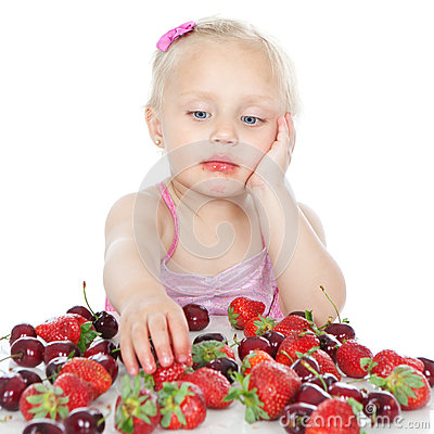 Little girl eating fruit on white