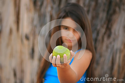 Little girl eating a green apple