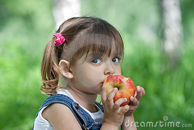 Little girl eating red apple outdoor
