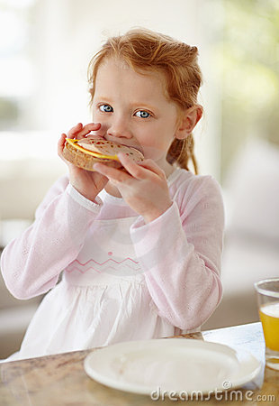 Little girl eating sandwich for her breakfast