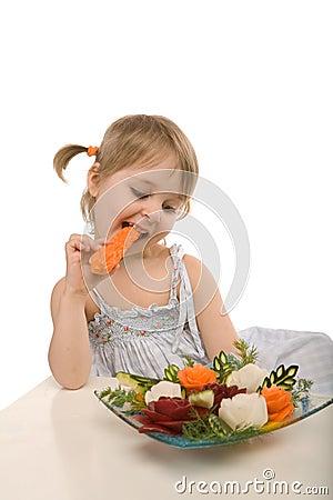 Little girl eating vegetables - chomping a carrot