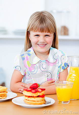 Little girl eating waffles with strawberries