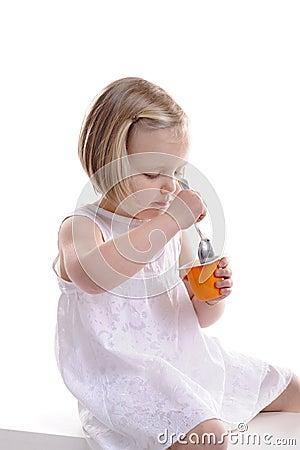 Little girl eating yogurt.