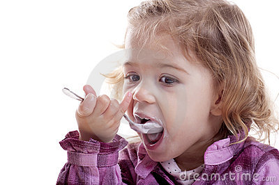 Little girl eating yogurt.
