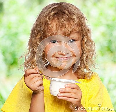 Little girl eating yogurt at summer