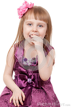 The little girl eats a candy
