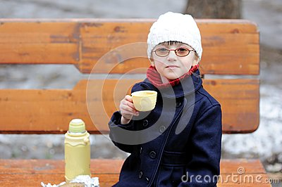 Little girl eats her lunch in the spring park