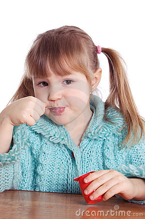 The little girl eats yoghurt