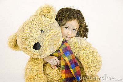 Little girl embraces a big teddy bear