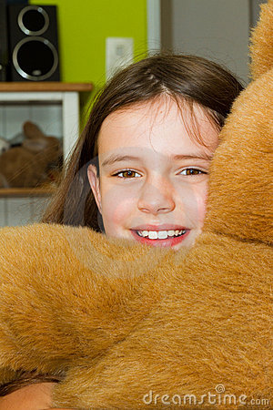 Little girl embracing teddy bear