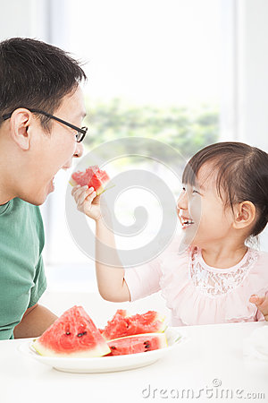 little girl with father eating fruits