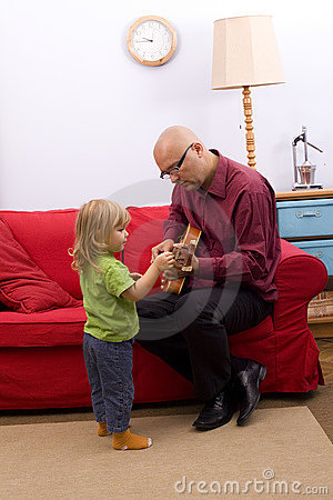 Little girl with father play electric guitar