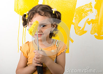 Little girl feeling happy while painting home wall Stock Photo