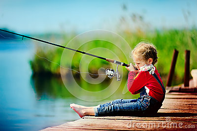 Little girl fishing from dock on lake