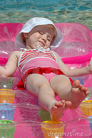The little girl floats on an inflatable mattress