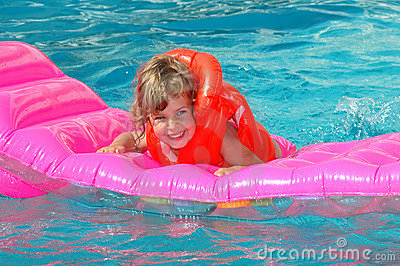 Little girl floats on an inflatable mattress