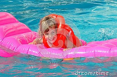 Little girl floats on an inflatable mattress