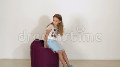 Swell Little Girl In A Fluffy Skirt Falls On Purple Bean Bag Sofa On White Background Fashion Cheerful Andrewgaddart Wooden Chair Designs For Living Room Andrewgaddartcom