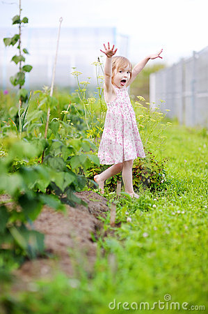 Little girl fooling around in a garden