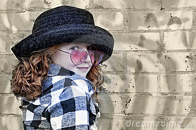 Little girl in front of brick wall
