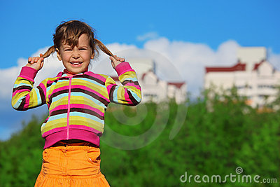 Little girl in front of trees and buildings