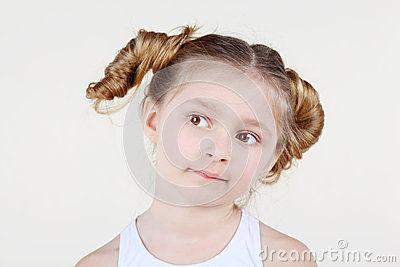 Little girl with funny hairdo looks into distance.