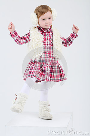 Little girl in fur headphones and vest dances
