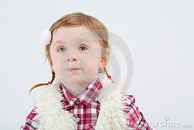 Little girl in fur vest grimaces and looks away