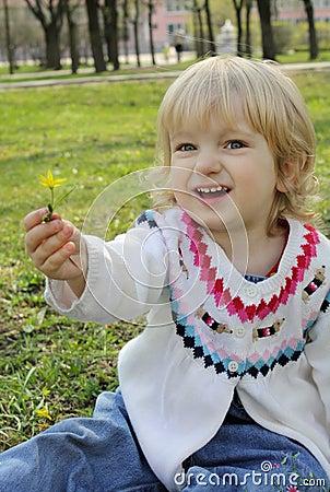 A little girl gives a flower
