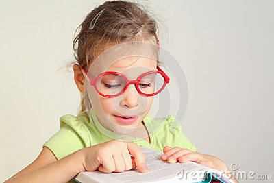 Little girl in glass put finger on text
