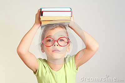 Little girl in glasses hold books
