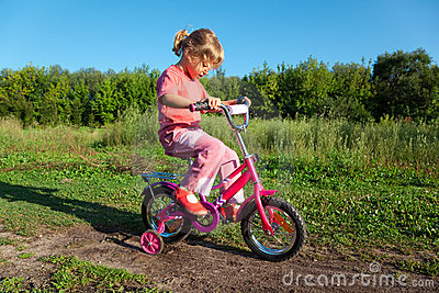 Little girl goes for drive on bicycle in park