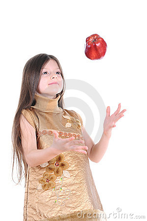 little girl in a gold dress catches a big red apple