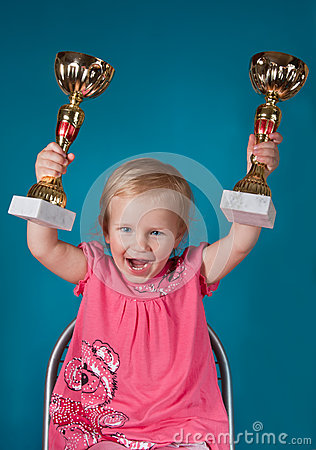 Little girl with golden trophies