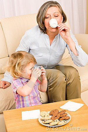 Little girl with grandmother eat cookies